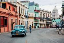 Bright orange building and blue car on Cuba tour