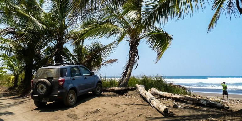 Car parked beside beach and palm trees in Costa Rica
