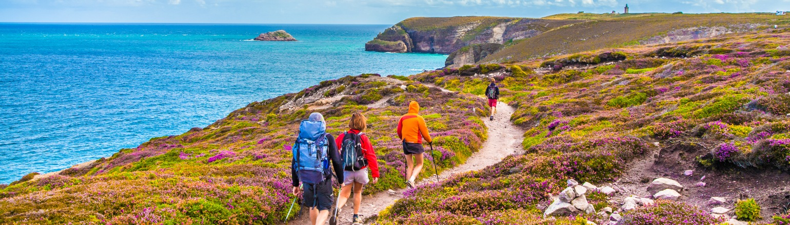Tourists hiking along the beautiful coasts of Bretagne at famous Cap Frehel peninsula viewpoint in France on Adventures within Reach tour