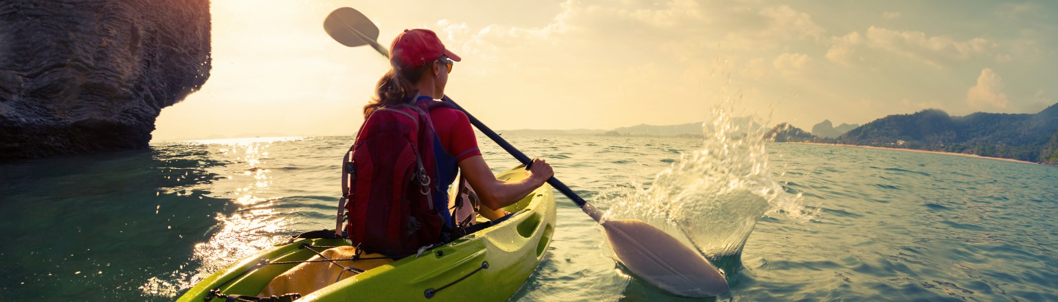 Young lady paddling the kayak near the cliff at sunset from Explore! tour