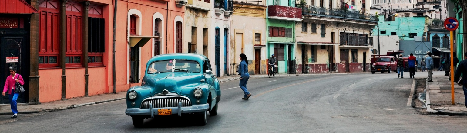 Historic old buildings and blue vintage car in Cuba