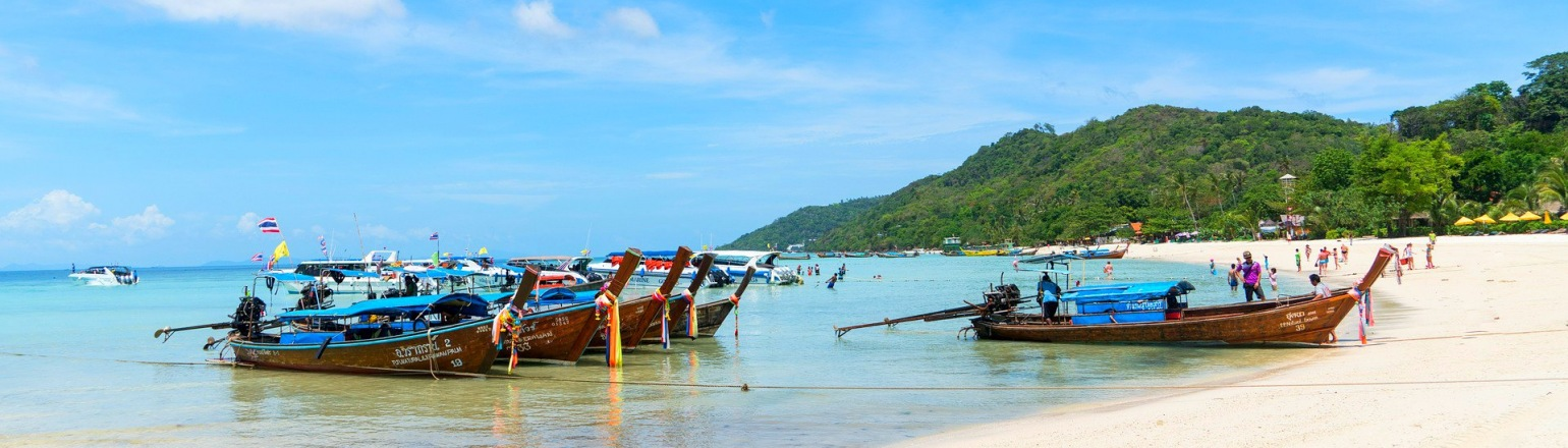 Traditional Thailand long boats waiting for passengers at the beach