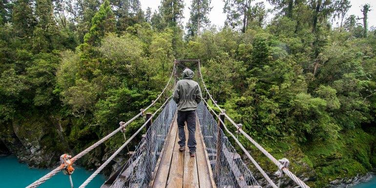 Traveler on hanging bridge over river in New Zealand