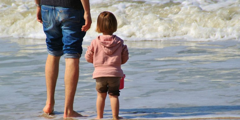 Father and young daughter on a beach