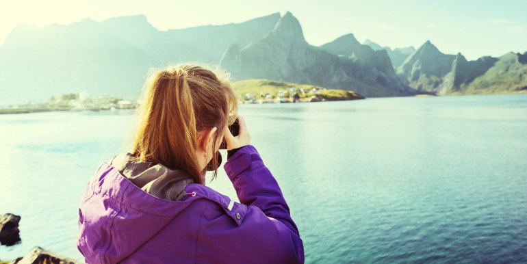 Young female traveler taking pictures of mountains