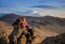 Young girl holding eagle on Mongolia tour