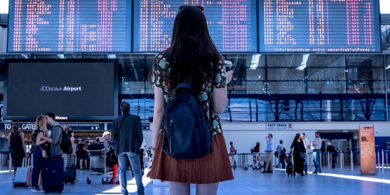 Young woman at the airport deciding where to go