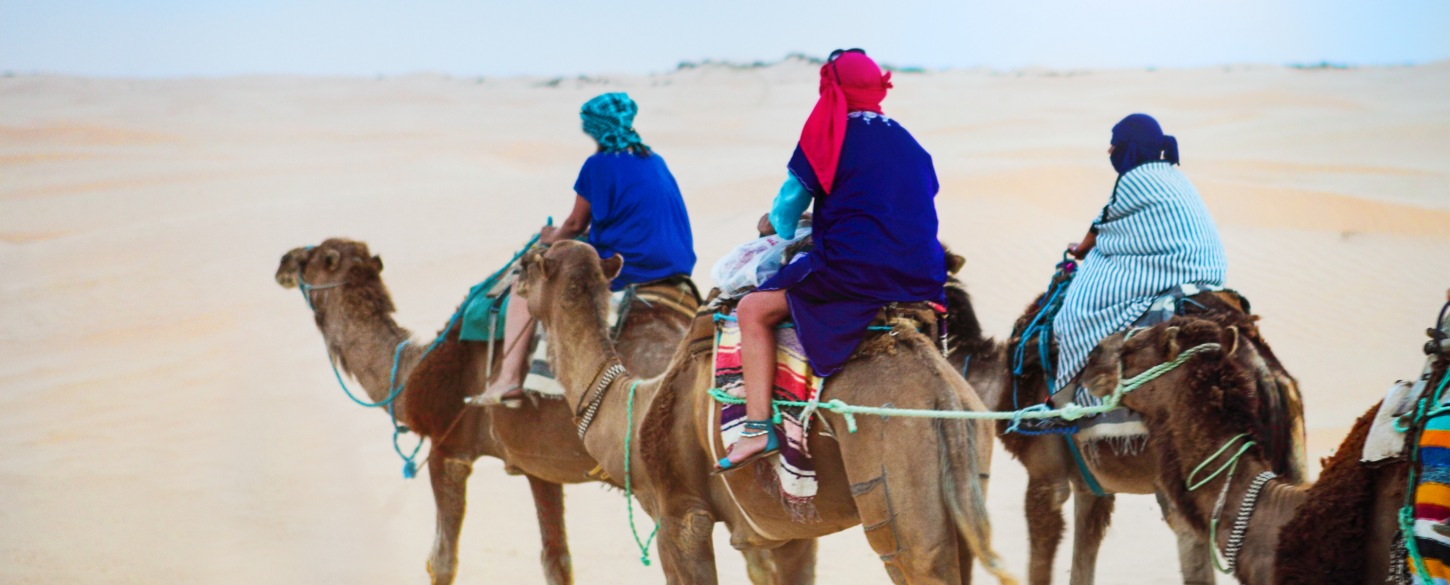 Experiential small group travel, riding camels in desert