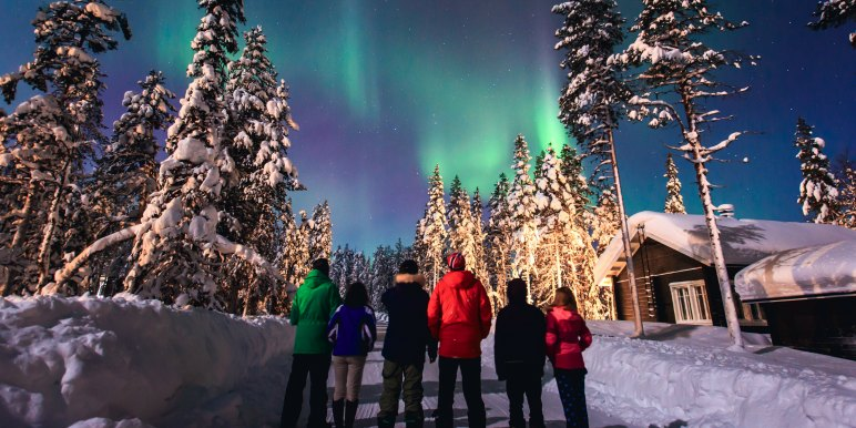 Family traveling in the arctic viewing the northern lights