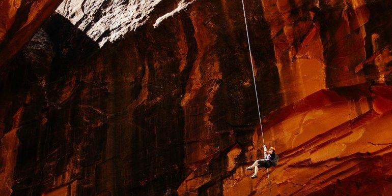 Adrenaline seeking traveler hanging off mountainside