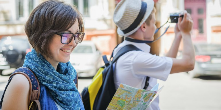 Young couple with map and camera traveling in Europe