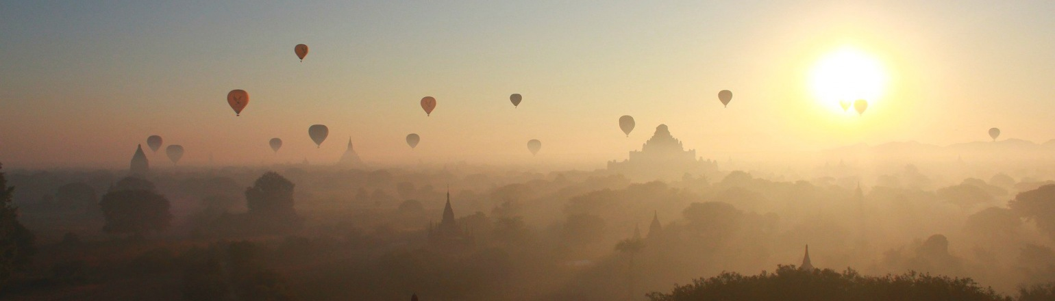 Sun setting over Bagan with hot air balloons silhouetted
