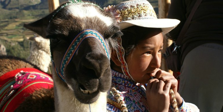 Young girl and llama in traditional dress in Peru