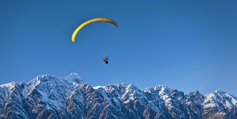 Solo skydiver over jagged snow covered mountains
