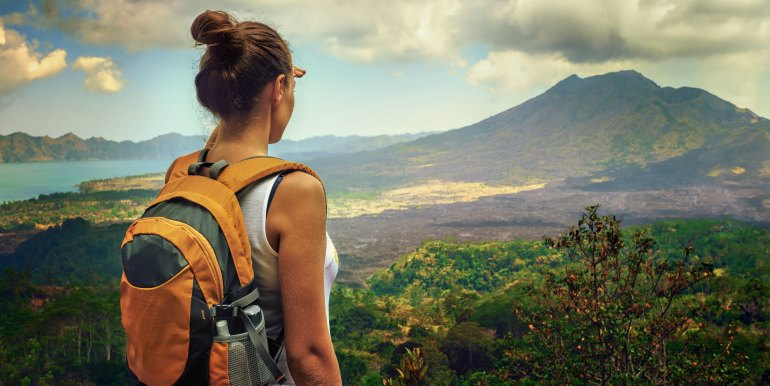 Young female hiker with backpack looking at volcano