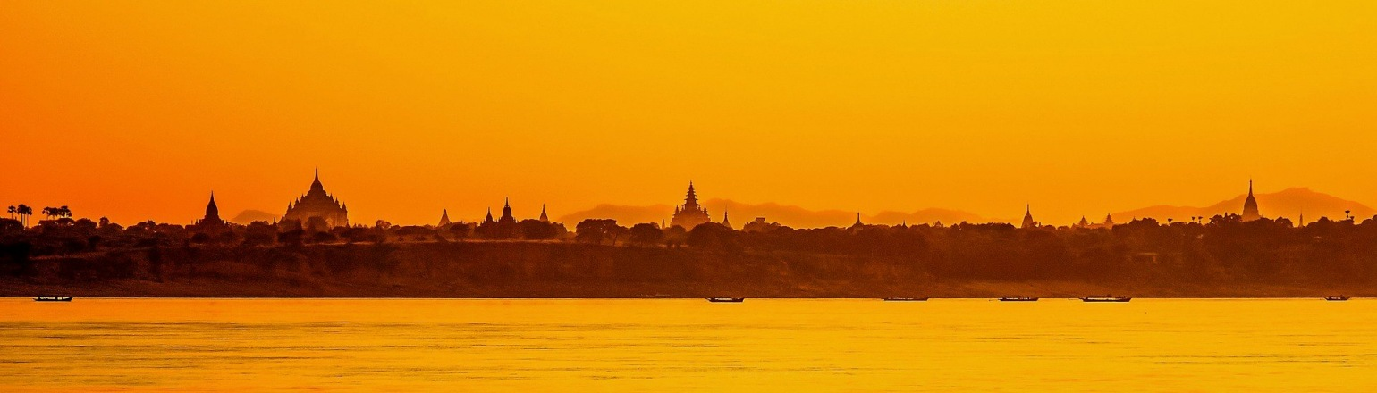 Bright orange sunset and temple complex silhouette along the Irrawaddy River