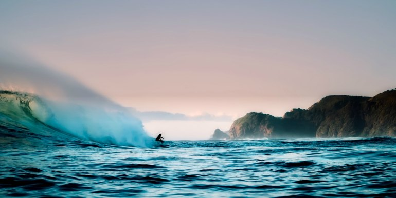 Solo surfer under big wave in New Zealand