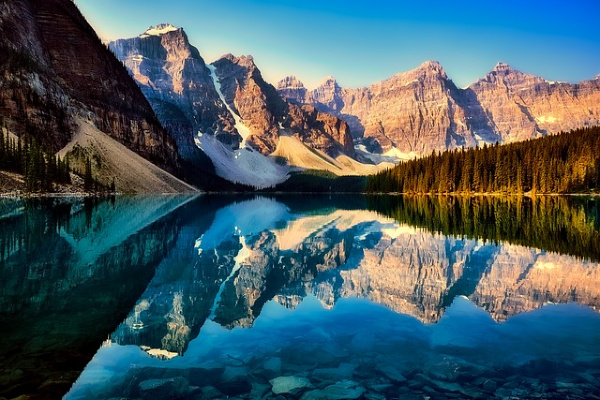 a landscape picture of snow capped mountains surrounding lake