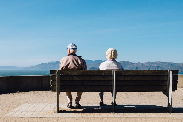 A senior couple sitting on a bench looking out at a lake